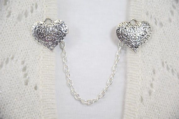 This elegant silver sweater pin that features silver hearts with an embossed pattern is the perfect accessory for a sweater. This also makes a great gift for the mom or girlfriend in your life. It would look great on a cardigan at the office or for a formal occasion such as a wedding or prom with a shawl or jacket. This is a classic cardigan clip that never goes out of style!