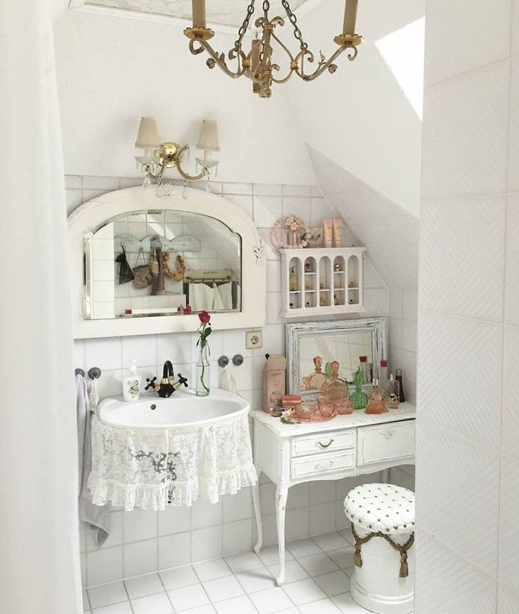 Lana Schuster's white-on-white bathroom mixes glossy ceramics with lace and distressed furnishings for a classic shabby chic style.