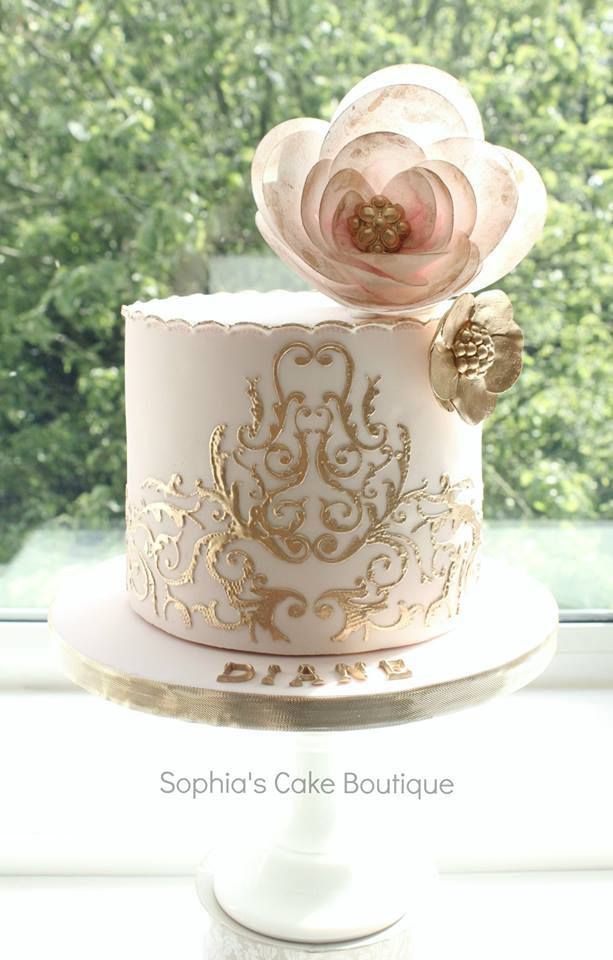 Beautiful gold detailing on this pretty pink and white cake.