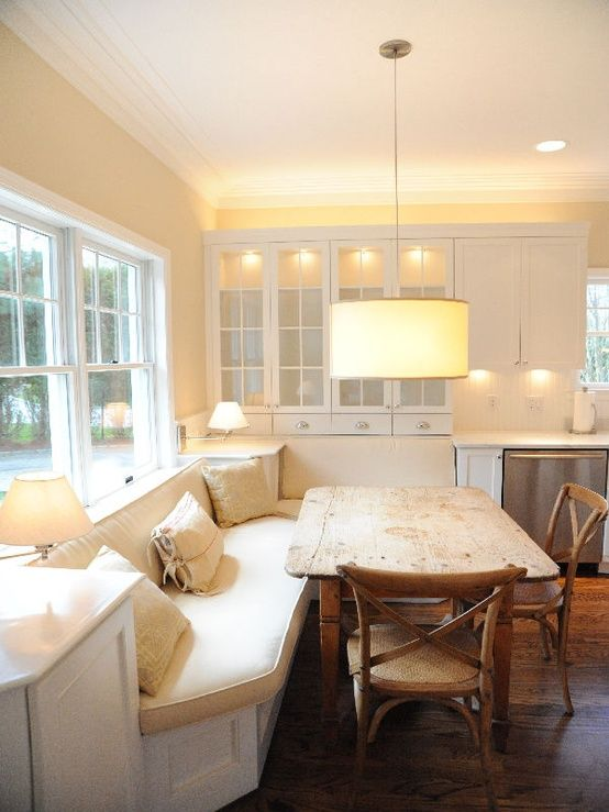 Old farmhouse kitchen table against a long banquette.