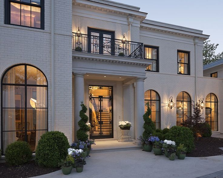 Stunning home featuring white brick exterior accented with arched steel and glass windows. Exquisite home with Juliet balcony over covered entry with Greek columns.