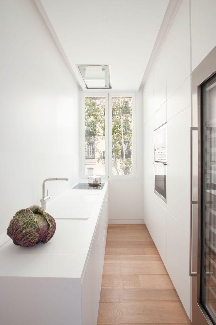 Эта Камбуз имеет минималистские белые шкафы с одной стороны для хранения, в то время как противоположная сторона современной кухне имеет столешницу, раковину и варочную панель.  Поскольку кухня белого цвета, свет от высоких окон в конце кухни отражает во всем пространстве, что делает его ярким и воздушным.