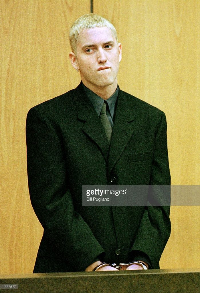 Rap artist Marshall Mathers III, a.k.a. Eminem, left, stands in handcuffs June 7, 2000 in the 37th district court in Warren, Michigan during his arraignment on charges of felonious assault and carrying a concealed weapon.