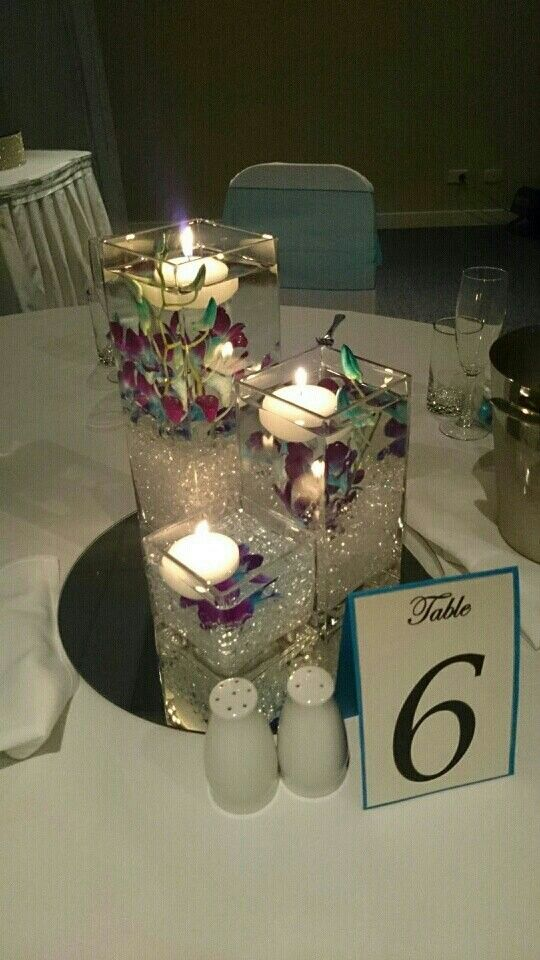 Perfect table centrepiece for a blue wedding. . Blue orchids and floating candles in 3 tier vases. #wedding #party #function #love #centrepiece www.astylishcelebration.com.au