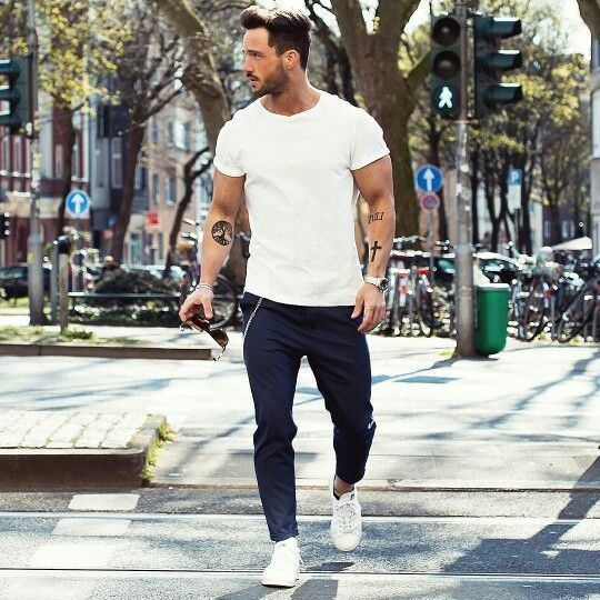 Consider pairing a white crew-neck t-shirt with navy trousers for a comfortable outfit that's also put together nicely. A pair of white plimsolls will seamlessly integrate within a variety of outfits. Shop this look on Lookastic: https://lookastic.com/men/looks/white-crew-neck-t-shirt-navy-chinos-white-plimsolls/19518 — White Crew-neck T-shirt — Silver Watch — Navy Chinos — White Plimsolls