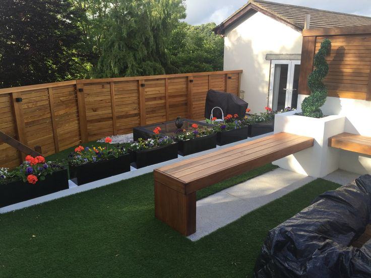 "Garden bench constructed using 4"" x 4"" posts then cladded with cedar fitted with LED lighting. False grass with a granite slab. Background fence powered with a LED strip lighting system below top plinth with black down lights."