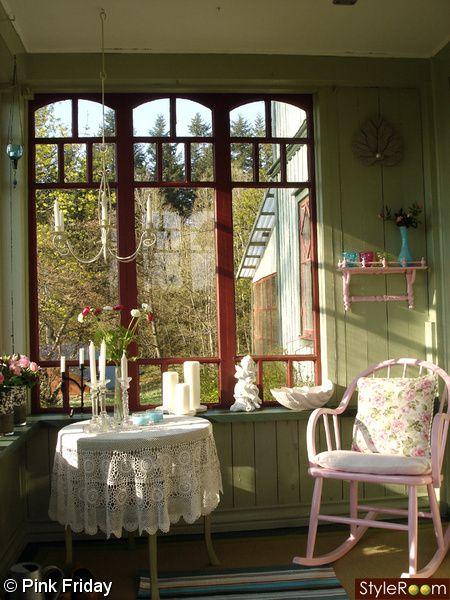 glasveranda,rosa stol,runt bord,lantligt,gröna väggar,gungstol