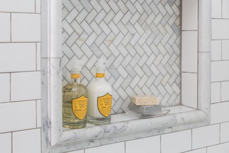 Beautiful master bathroom boasts a walk-in shower clad in white subway tiles accented with dark grout fitted with a Arabescato Carrera Marble tiled shower niche framed with marble pencil tiles.