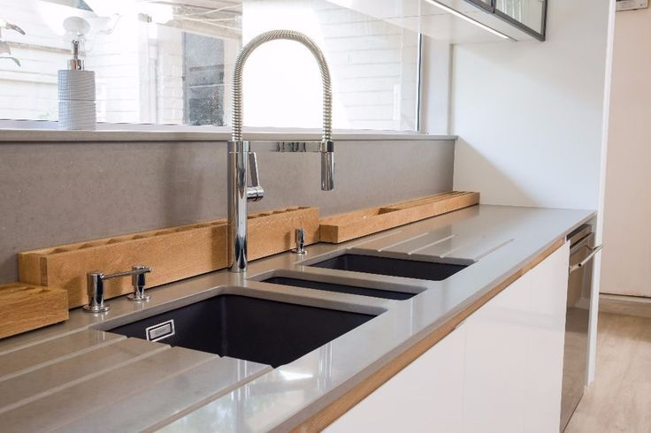 The sink area incorporates three Blanco sinks, each supplied by Uber Haus. The area includes a Blanco tap and a soap dispenser. The contrast of the striking, dark sinks against the worktops creates an impressive statement, particularly with the distinctive, milled drainage grooves. Our Uber Haus team also designed and manufactured a custom drip tray, which sits behind the sinks.