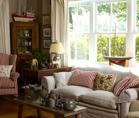 Country Style Living Room  Ticking and red check fabric are classic choices that further the cottage aesthetic.  Antique furnishings, casual fabrics, vintage collectibles and folk art pieces come together to create an eclectic and cozy living room.