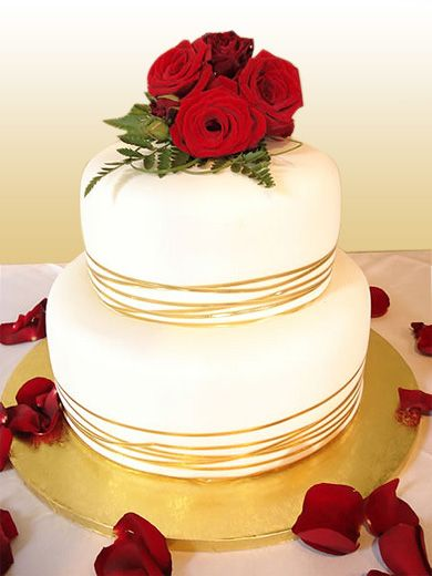 traditional white Wedding cake, fine gold ribbon, red roses.