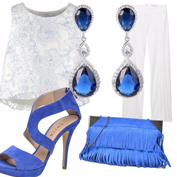 Top corto bianco con fantasia di rose celeste-bianco, pantaloni a vita alta bianco con cuciture lungo i lati, sandalo alto blu elettrico scamosciato, borsa particolare scamosciata con frange blu elettrico, orecchino importante pandente con pietre blu