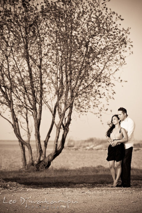 engaged couple in a romantic pose, by a tree.