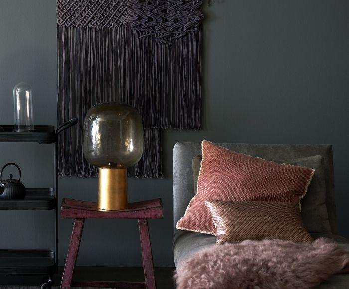 Donkere interieurs zijn hot op dit moment. Deze matte grijze muur vormt een sobere mysterieuze achtergrond voor de vele rood en roze tinten. Het glamour  romantische gevoel, zit m vooral in het gebruik van fluweel, bont en messing.