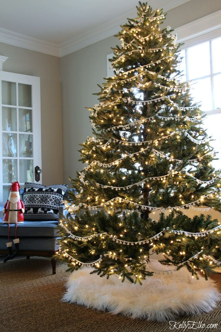 Christmas Home Tour - love this tree with pom pom garland and fur tree skirt from HomeGoods kellyelko.com sponsored pin #ChristmasTree #christmas