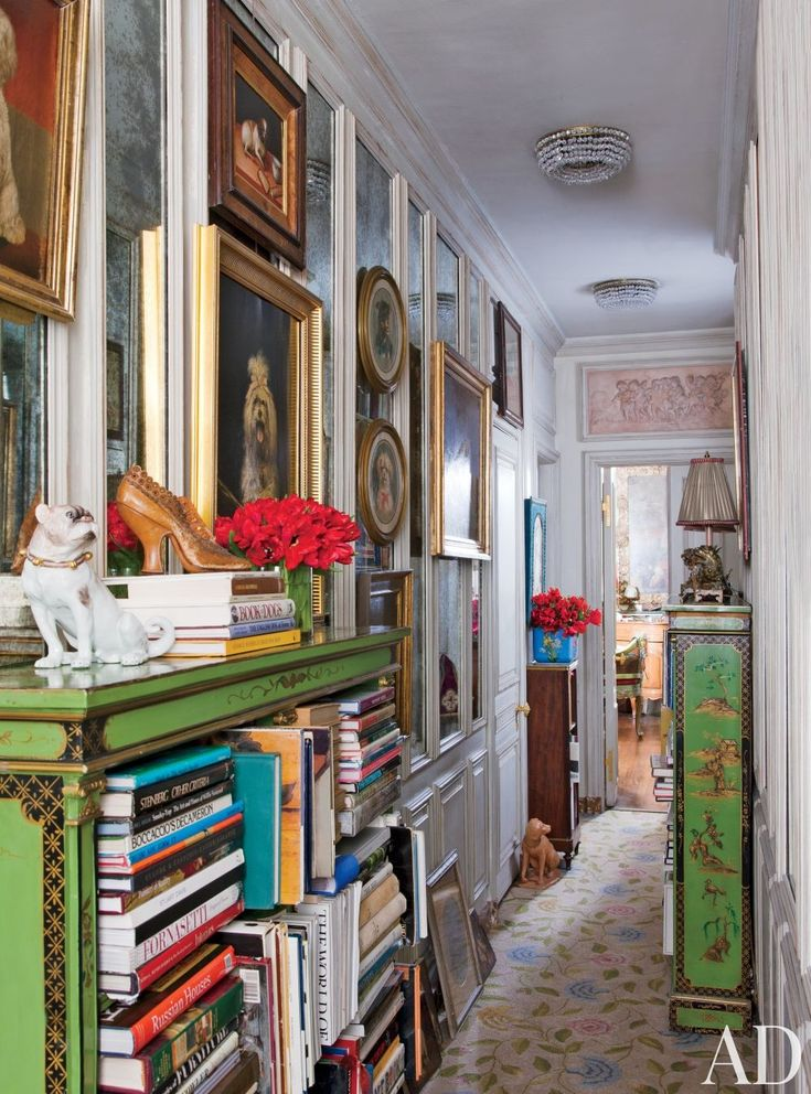 A hallway in Iris Apfel's New York apartment is lined with dog paintings and 19th-century English bookcases.