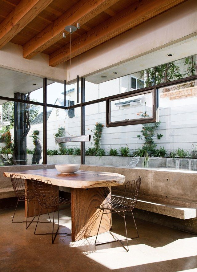 """The details that Ford credits for making the home special—""""a mixture of woods, the use of concrete, and the massive windows that bring the outside in""""—are on full display in the dining area. A beamed ceiling creates a cozy shell for the live-edge table from HD Buttercup and the concrete built-in bench. The chairs are vintage Harry Bertoia.   archdigest.com"""