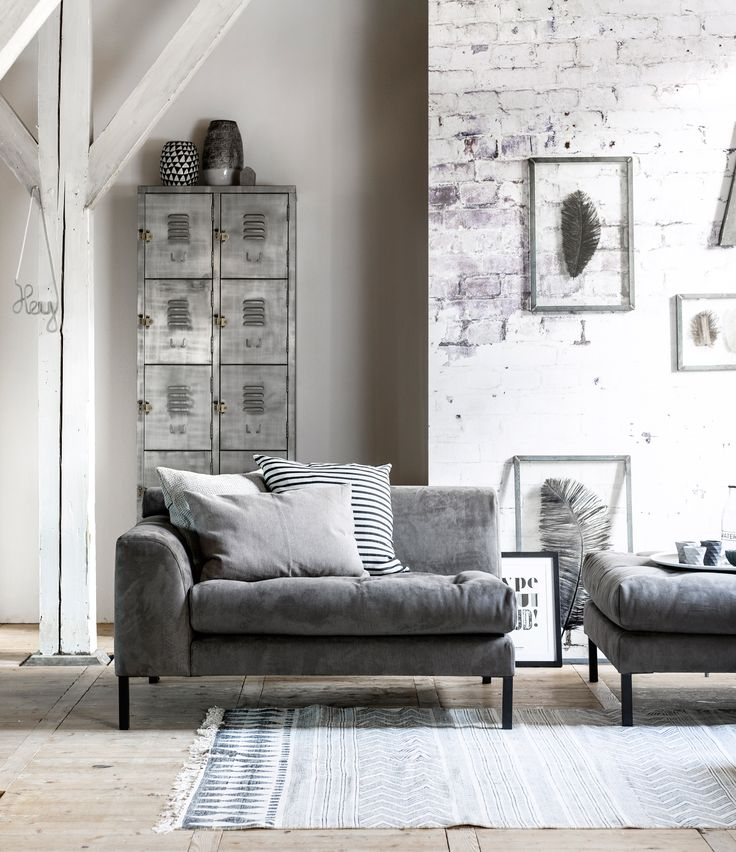 Black white and grey living room with grey couch elements Brave by vtwonen, locker by De Troubadour and rug by Livv Lifestyle, feather picture frame, accessoires by Nijhof, het Kabinet and Six and Sons.| Styling Kim van Rossenberg | Photographer Sjoerd Eickmans | vtwonen May 2015 | #vtwonencollectie