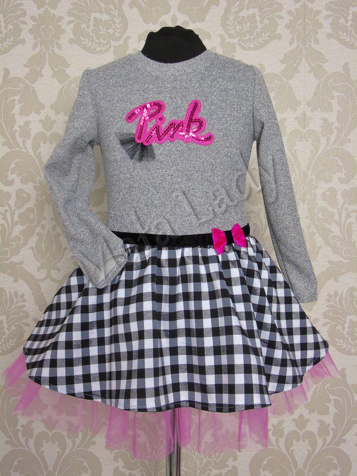 Sukienka Pink w czarno-białą kratkę z szenilu połączona z szarą dresówką bawełnianą. Dół kreacji wykonany z tiulu w kolorze różowym, odszytego podszewką. Przepasana z przodu czarnym paskiem w pasie z małą kokardą z boku. Sukienka posiada długie rękawy oraz kryty zamek z tyłu kreacji.Sukienka dostęna również z dodatkami w kolorze czerwonym oraz czarnym.