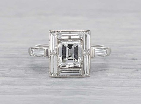 Antique Art Deco engagement ring made in platinum and centered with an EGL certified approximately 1.40 carat emerald cut diamond with F-G color and VS2 clarity. Accented with eight baguette cut diamonds weighing approximately one carat total. Circa 1930.