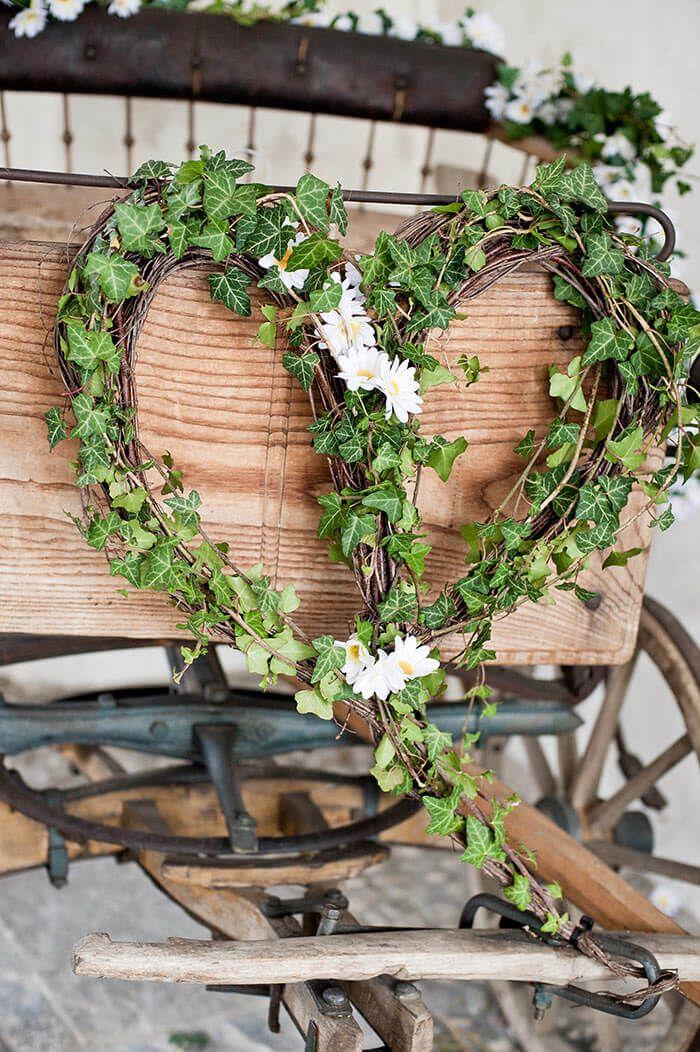 Herzförmige Hochzeitsdeko mit grünem Efeu und weißen Blümchen - angebracht an einer Hochzeitskutsche.