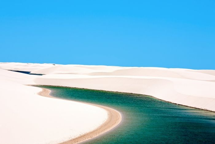 The combo of startlingly white sand and deep blue, clear water makes the landscape of the Lençóis Maranheses National Park in north-east Brazil a striking view. This is Brazil's desert, but because Brazil doesn't have a desert climate the dips between the vast sloping dunes fill up with water during the wet season.