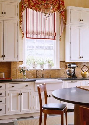 This detailed valance is trimmed in plaid with an overlay of silk tassels that echo the fabric's red, ivory, and green hues. Because the windows in this kitchen are high, an elegant treatment remains safe from water splashes at the sink./