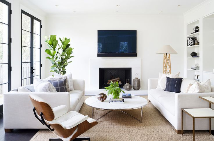 Gorgeous black and white family room with urban chic style by Ella Scott Design. Black painted French doors open to the outdoors. Come see the dramatic Before & After: Fussy Traditional to Urban Chic! #blackandwhite #familyroom #moderndesign #benjaminmooremoonlightwhite #whitesofa #eameschair #midcenturymodern #urbanchic