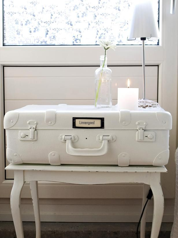all white suitcase beside table