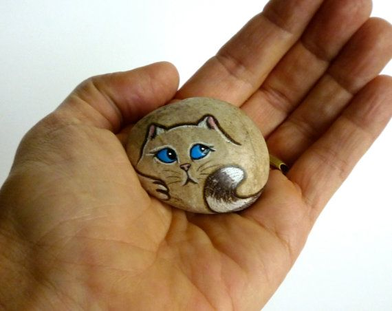 Up for adoption is a hand painted Petrified Pet. I try to leave as much of the natural rock as possible. It makes it much more interesting when you can see the texture and color of the rock. I use a special technique to paint the eyes so they appear 3 dimensional. Because of this technique this cat does not like to live outdoors. (Covered porch is acceptable).  Hell be happy inside the house on a window sill, by the fireplace or as a paper weight .  Hes signed and dated on the back and I…