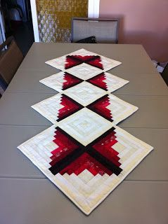 Esther Ramos- log cabin pattern quilted table runner with colors on the inside and white on the outside.