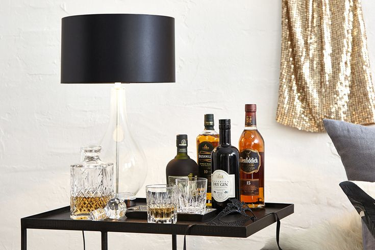 Beautifully styled side table with a dark lamp and a mini bar. We love the elegant and festive look of this living room. The glittery party dress, the black mask and the and the high-proof alcohol a splendid atmosphere - perfect for the holiday season. Check out our website to see more pictures!