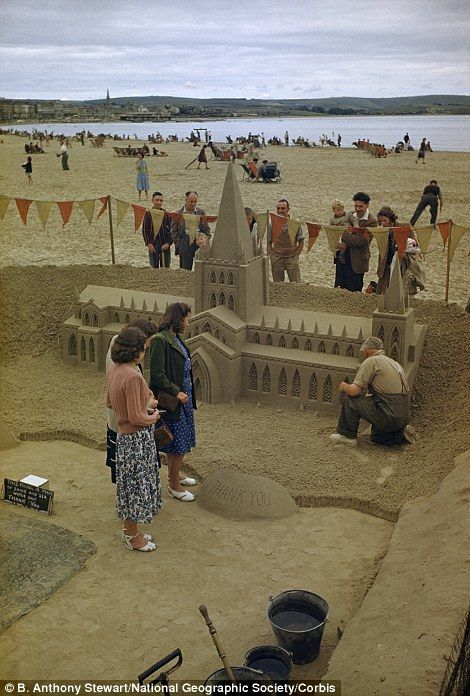 Sands of time: People watch a sculptor build a miniature cathedral on Weymouth beach, Dorset