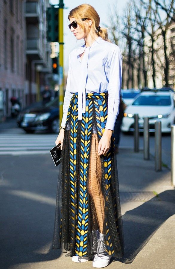 Veronika Heilbrunner wears a blue pussy bow blouse with a printed lace car wash pleated skirt and Nike sneakers
