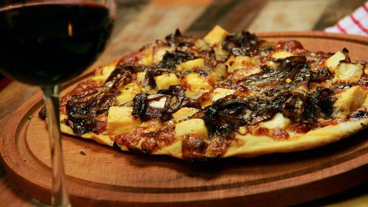 Receta con instrucciones en video: ¡Prepara una pizza gourmet en tu casa! Ingredientes: Para la masa:, 30 gr de levadura, 1 cda. de azúcar, 1/2 taza de agua tibia, 1 kg de harina, 20 gr de sal, 6 cdas. de aceite, Agua c/n, Para el armado:, Salsa de tomate, 100 gr de queso mozzarella, 50 gr de queso parmesano, 100 gr de queso de cabra, 1 kg de cebolla, 100 ml de vino tinto, 50 ml de miel de abeja, Aceite de Oliva