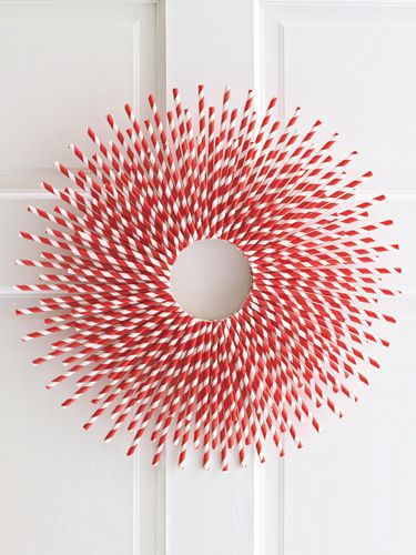 """Straw-Burst: It may just be red and white, but this wreath pops like no other—and it couldn't be more affordable, since it's crafted out of plain paper straws. Materials • Pencil • 6"""" flat floral and craft ring (99¢; Michaels.com for stores) • 1 sheet of white paper • Scissors • Hot-glue gun and glue sticks • 1 box of 144-count paper straws • Ribbon scrap Step by step instructions"""