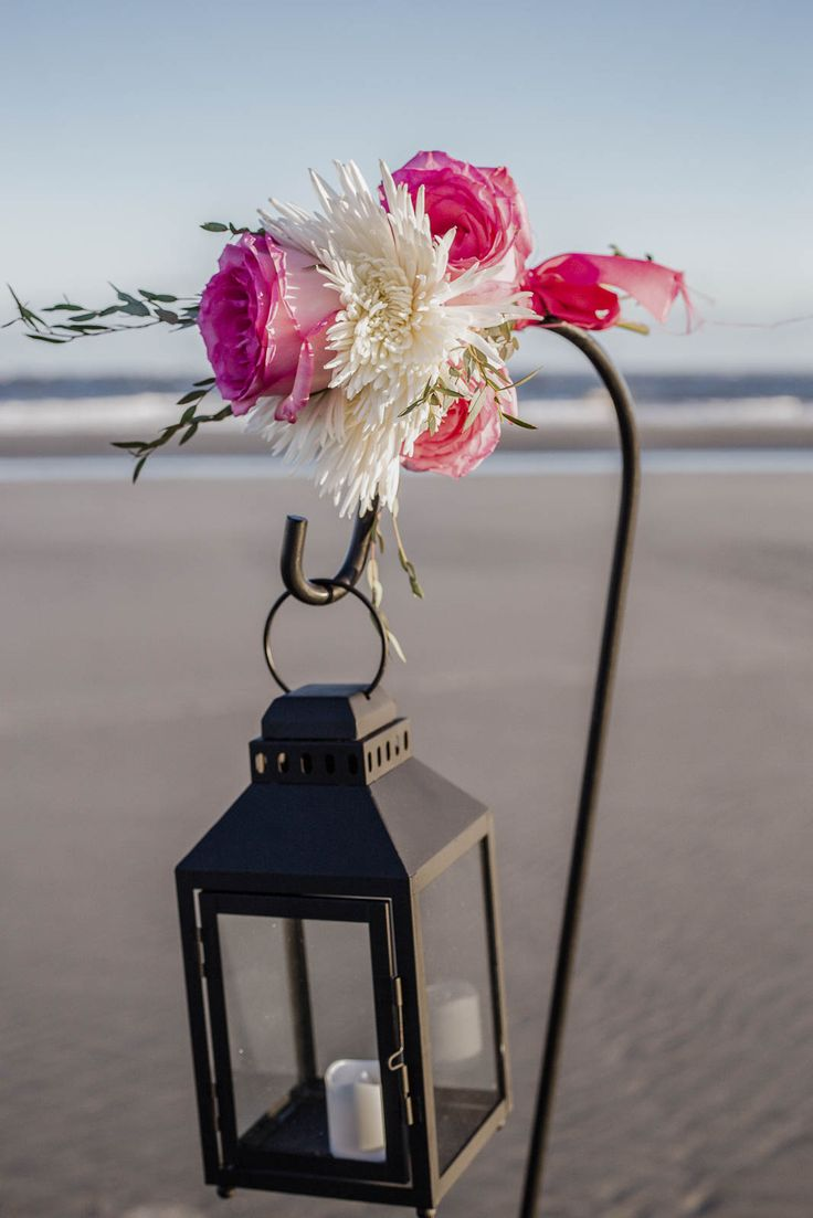 aisle decoration of lantern with a candle and flowers tied to the shepard hook by Reynolds Treasures