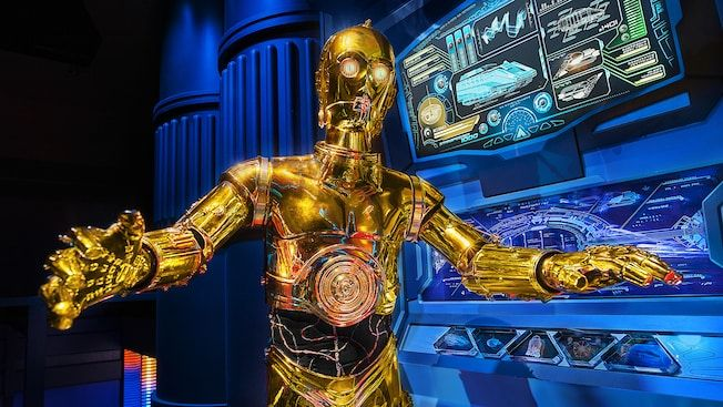 C-3PO stands near a computer screen showing the schematics of a Starspeeder 1000 spacecraft