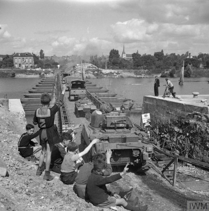 Children wave as a Sherman tank and vehicles of 152nd Brigade, 51st Highland Division, cross a pontoon bridge over the Seine at Elbeuf, 2 September 1944.