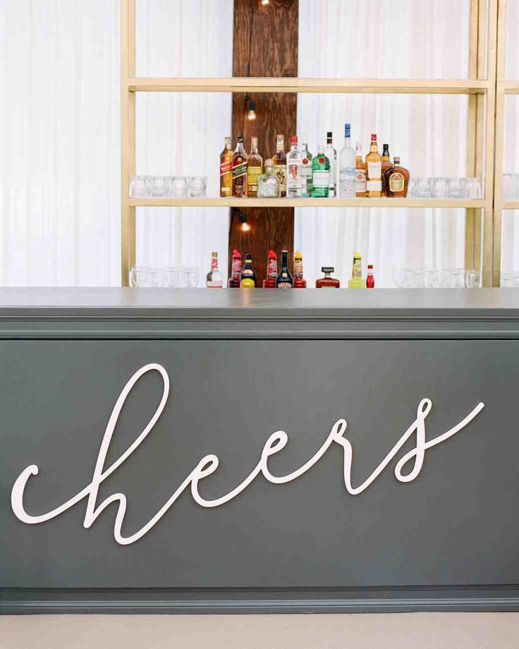 "It Was Back-to-Back Weddings for This Couple in St. Louis | Martha Stewart Weddings - A painted wooden ""cheers"" sign, modeled after the loose script used on the stationery, was custom-made for the bar."