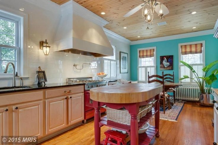 An eclectic kitchen with a small oval island with shelves for storage. It also comes with a wooden ceiling with a fan and chandelier, pin lights, blue and green walls, cabinets, appliances and wooden flooring boards. Plants, fruits, and a rooster painting, small iron frame are added for decoration.