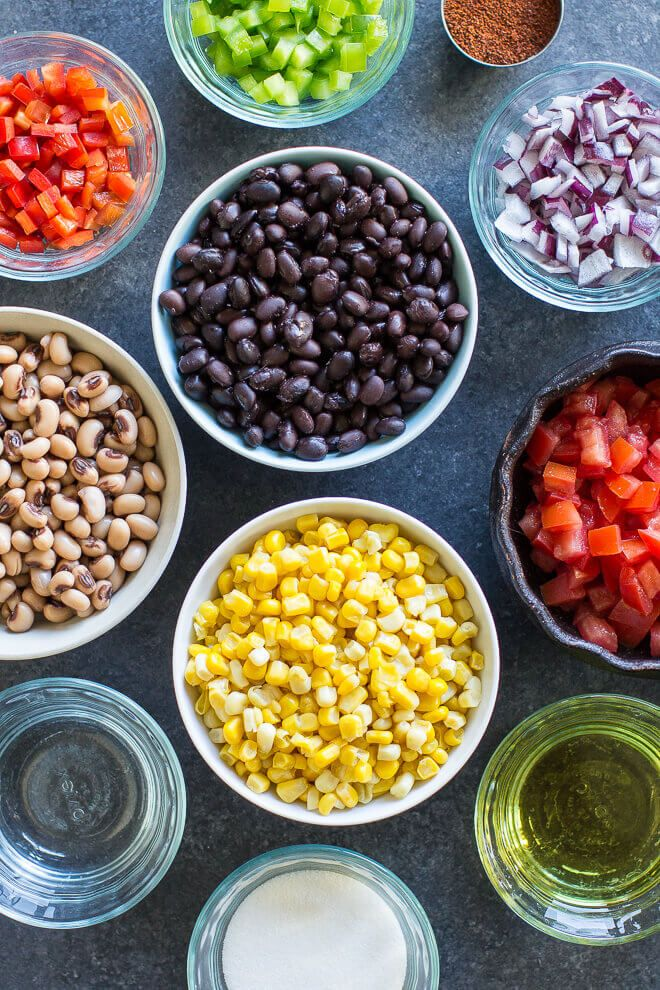 8 bowls of ingredients for Cowboy Caviar. Clockwise from top: bowl of black beans, chopped red onions, chopped tomatoes, olive oil, sweet corn kernels, white wine vinegar, black eyed peas, red bell pepper.