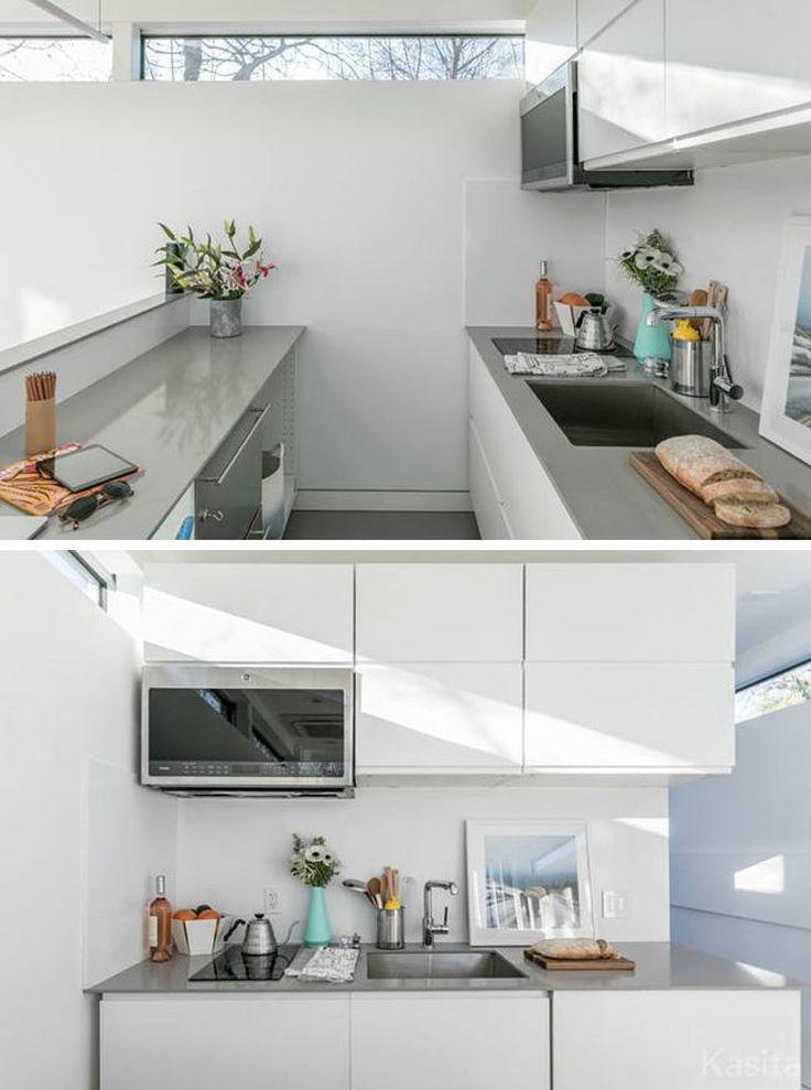 この小さな白い灰色のキッチンには2バーナーの誘導式クッキングトップと対流式電子レンジ、さらに多くの収納スペースと2つのカウンタースペースがあります。