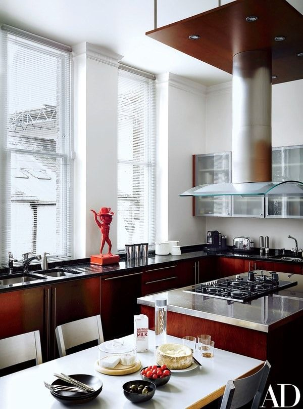 The kitchen's cabinetry, stainless-steel counter, hood, and table are all by Poggenpohl   archdigest.com