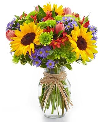 "Garden Bouquet $59.99 Celebrate the beauty of a mixed flower arrangement including sunflowers, pink Tulips, Red Alstroemeria, Purple Monte Casino Asters and green poms in clear vase wrapped in raffia.Measures 12""H b x 10""L. Flowers are arranged and hand delivered through one of our Network Florists during normal business hours.Same Day Handling and Service Fee $18.95, Order before 10 am Eastern."