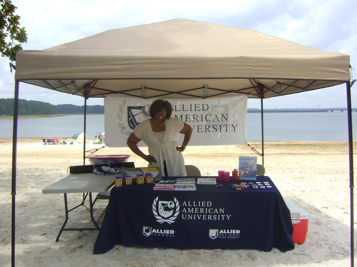 Belinda Henderson smiling in front of the Allied American University booth at Fort Gordon's family fun day #onlineuniversities #USArmy