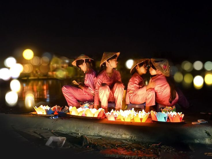 Young girls selling floating candles in Hoi An, Vietnam. Photograph by Fabio Manca
