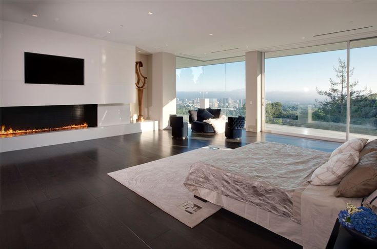 Gorgeous big master bedroom interior with all you need to be happy: an inspiring view, a comfy master bed, a modern television and, of course, the perfect fireplace for winters | Discover more: http://masterbedroomideas.eu/