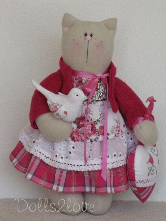Tilda Cat Polly wearing a pink liberty fabric and checkered dress and a pink jacketbholding a lovely bird and a hand-embroidered heart made by Dolls2love on Etsy, €65.00. (sold)