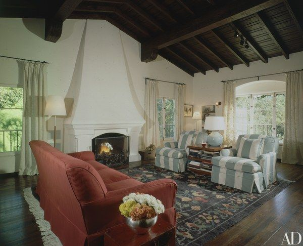 The living room in the Los Angeles residence of actress Jamie Lee Curtis and her husband, actor and director Christopher Guest, features dark wood floors and beams offset by white walls; the home was decorated by Jan McFarland Cox.